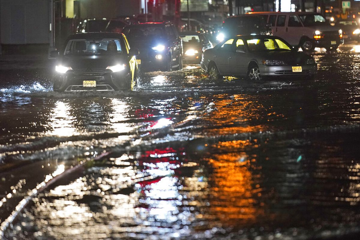 Cars make their way through flooded streets in Teterboro, N.J.