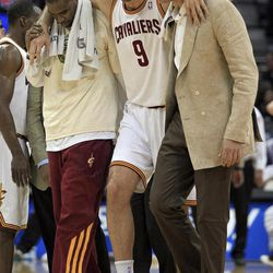 Cleveland Cavaliers' Semih Erden, from Turkey, is helped off the floor by Antawn Jamison, left, and Anderson Varejao after injuring his ankle in the second quarter of an NBA basketball game against the Indiana Pacers on Wednesday, April 11, 2012, in Cleveland.