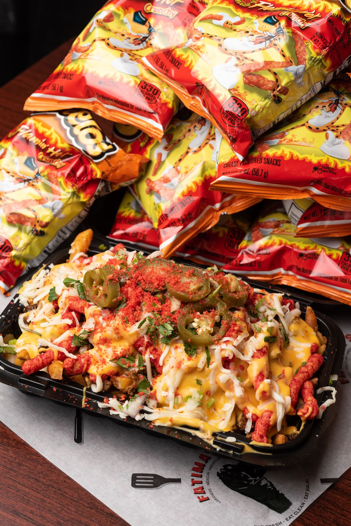Fries topped with nacho cheese and Hot Cheetos inside of a restaurant.