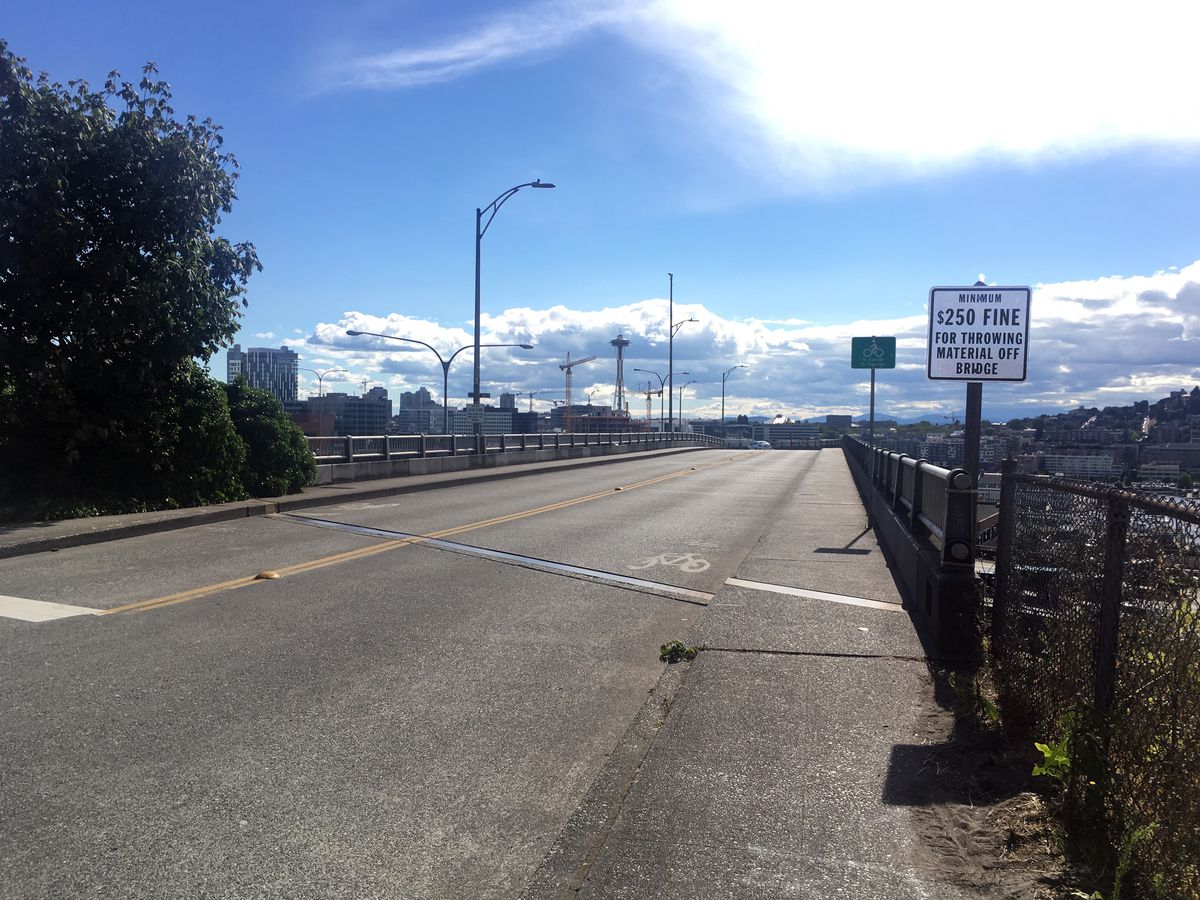 The entrance to a freeway overpass on a sunny day. A sign to the right warns of a fine for throwing stuff off the bridge. There are cranes and skyscrapers in the background.