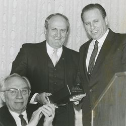 BYU head football coach LaVell Edwards is honored by Elder Thomas S. Monson, now president of The Church of Jesus Christ of Latter-day Saints, and Elder Gordon B. Hinckley on Dec. 13, 1984.