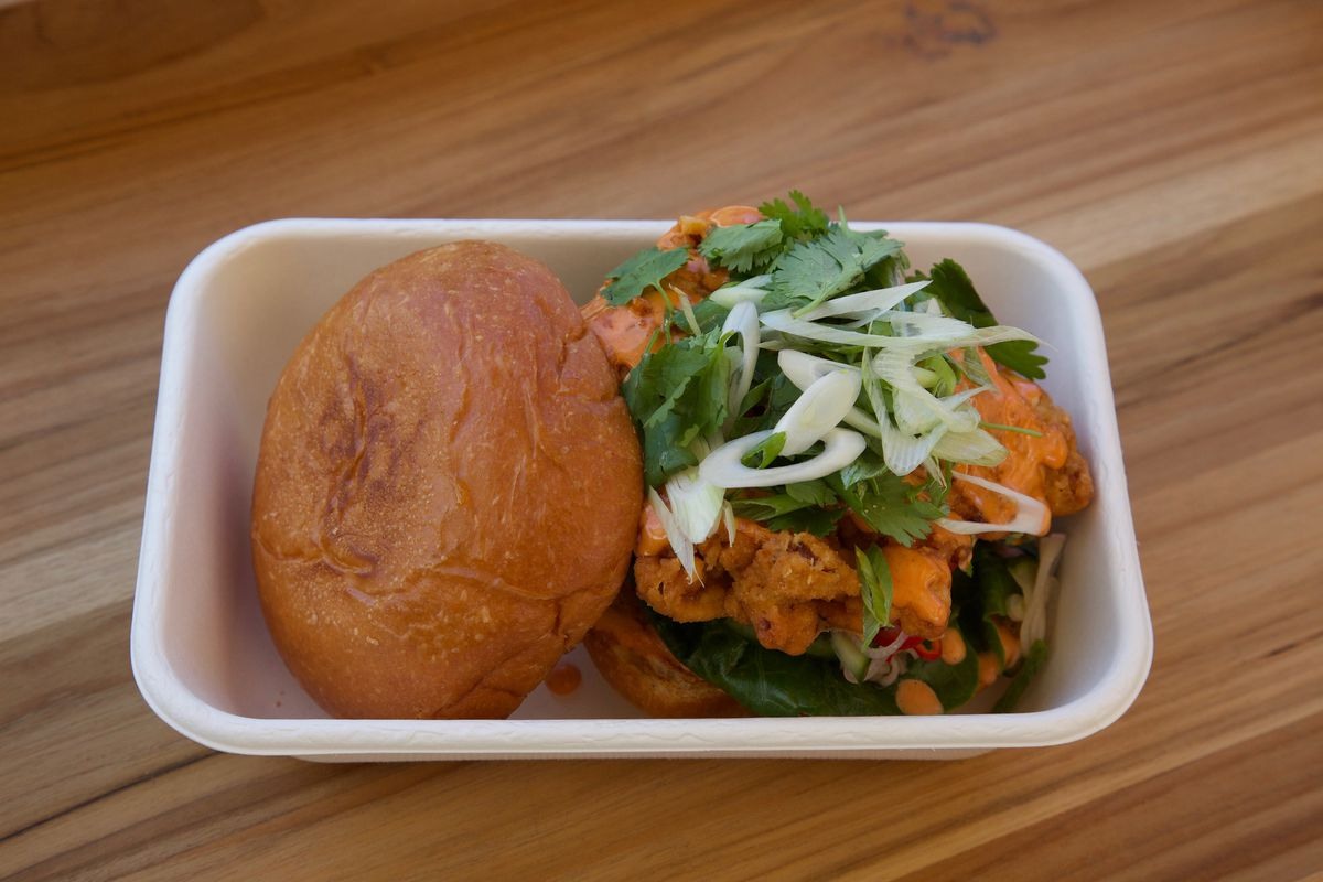 Kin Khao's fried chicken sandwich, topped with herbs, cucumber salad, and Sriracha aioli