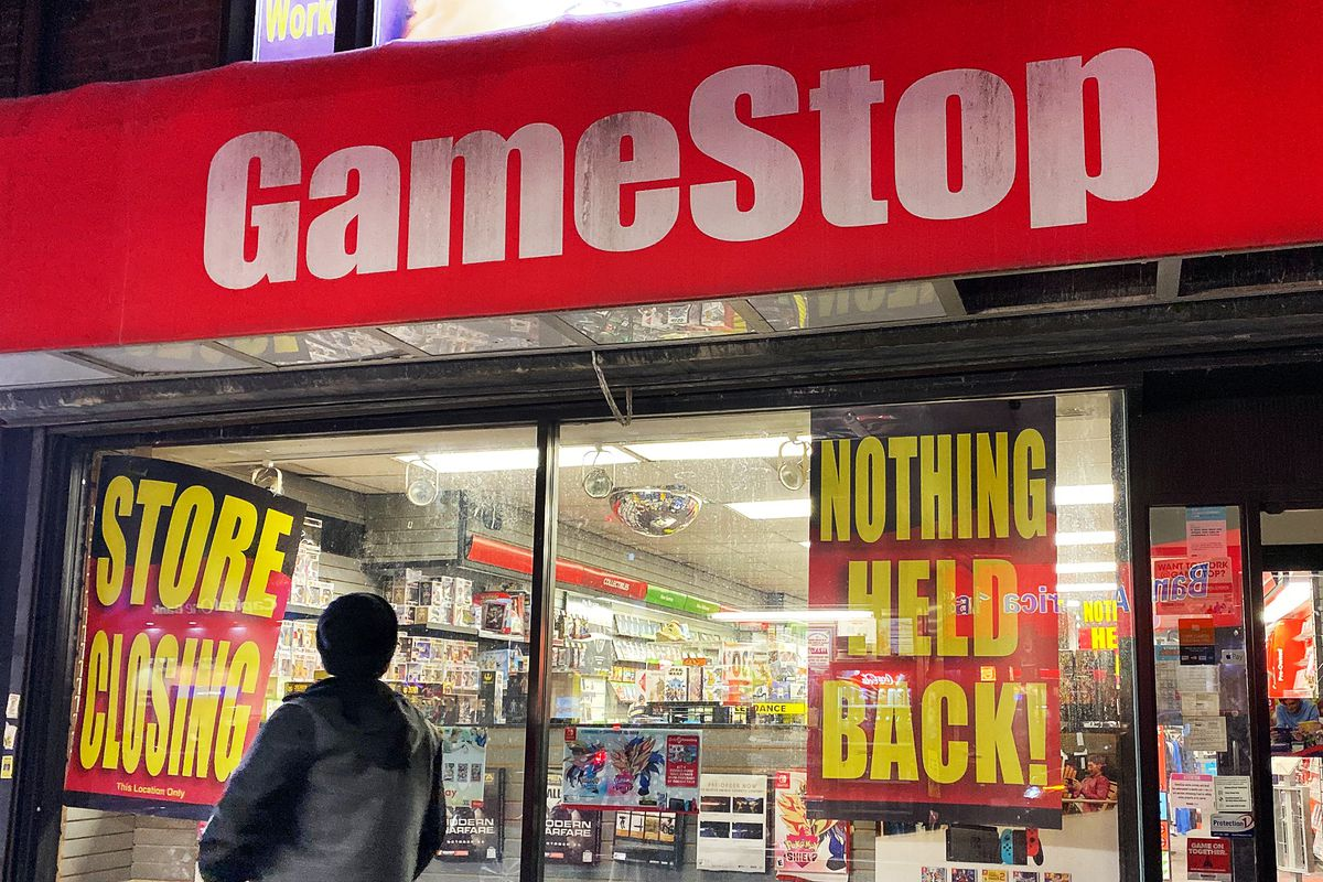 """person walking past a very depressing-looking GameStop store with """"STORE CLOSING"""" and """"NOTHING HELD BACK!"""" signs in the front window"""