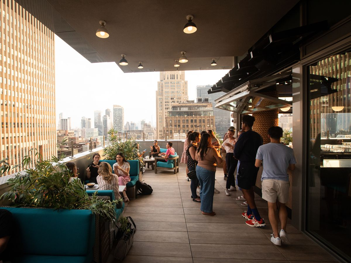People mingling around a bar and in booths on a rooftop restaurant with the city in the background.