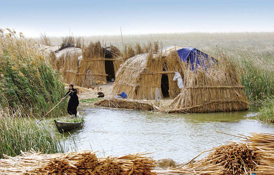 An image of two houses made from reeds n a marsh. A woman stands in a paddle boat.