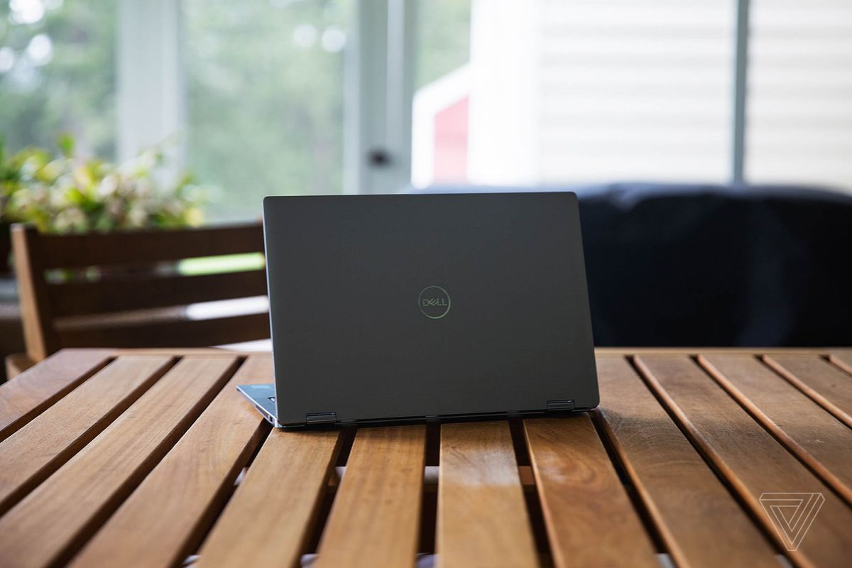 The Dell Latitude 9420 facing away from the camera, angled slightly to the left, on a porch table.