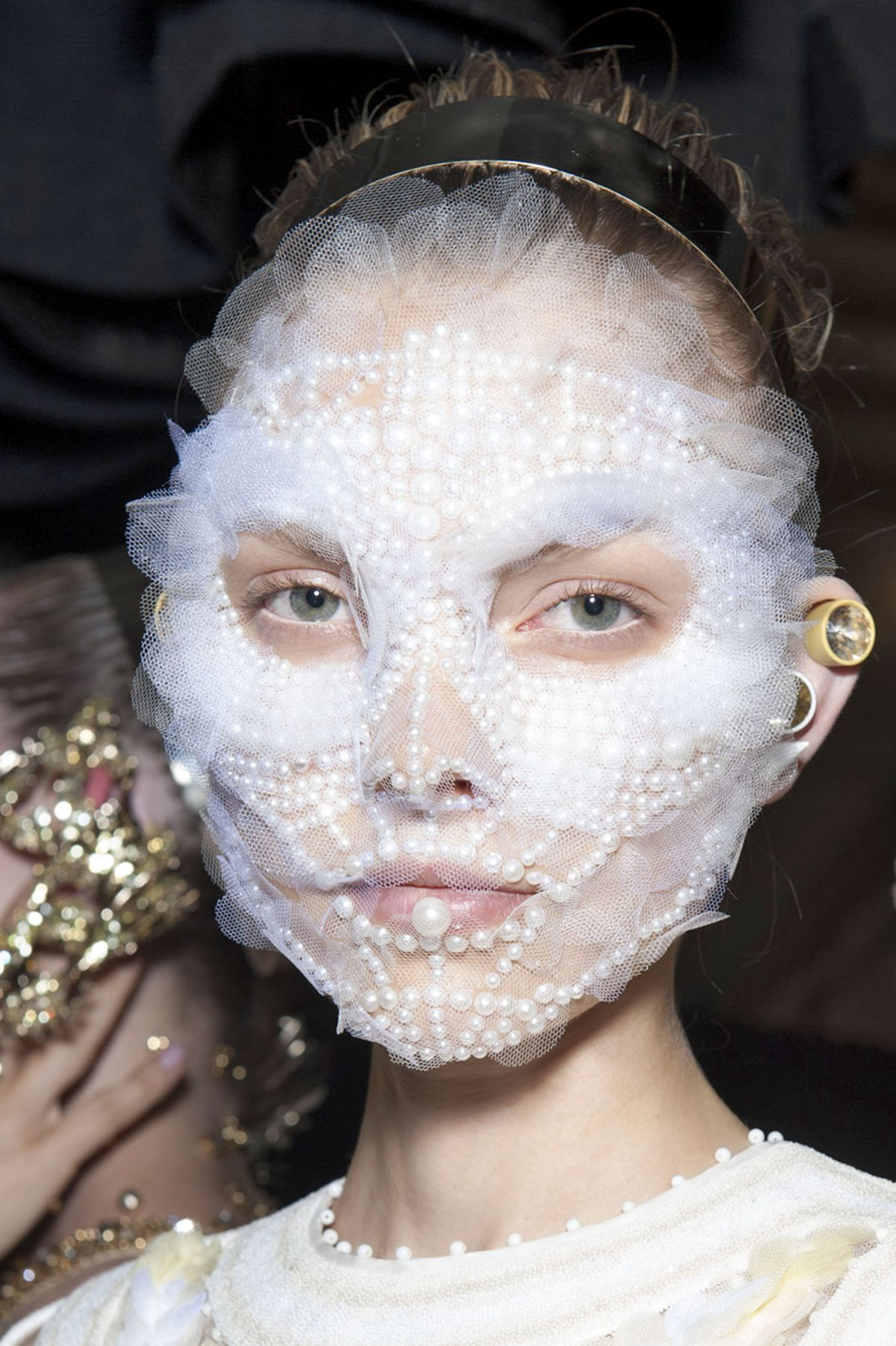 A model wears a pearl-and-lace mask backstage at a Givenchy runway show.