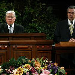 Elder M. Russell Ballard, left, gives his talk at the Hispanic devotional, with Omar Canals translating. Elder Ballard urged the audience to share message of the church.