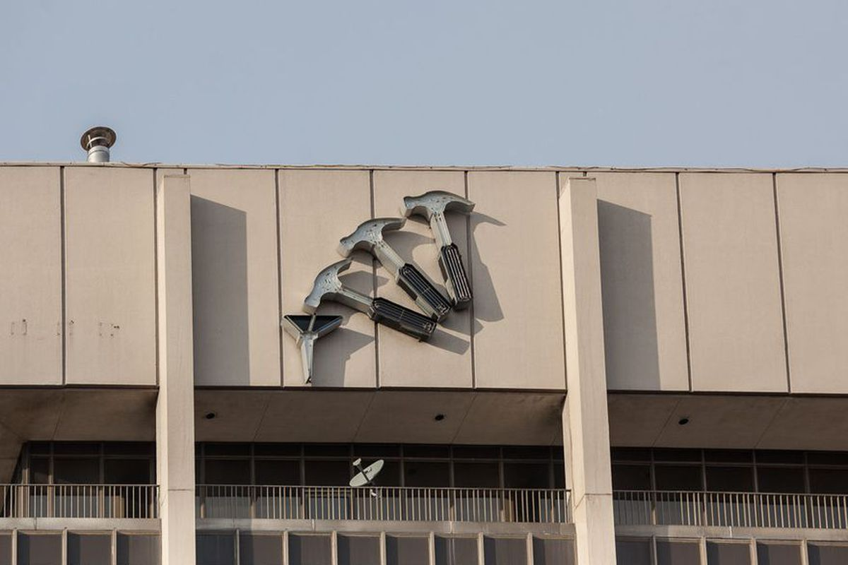 A hammer and nail sign on the side of the Professional Plaza building, prior to being taken down by the Roxbury Group.