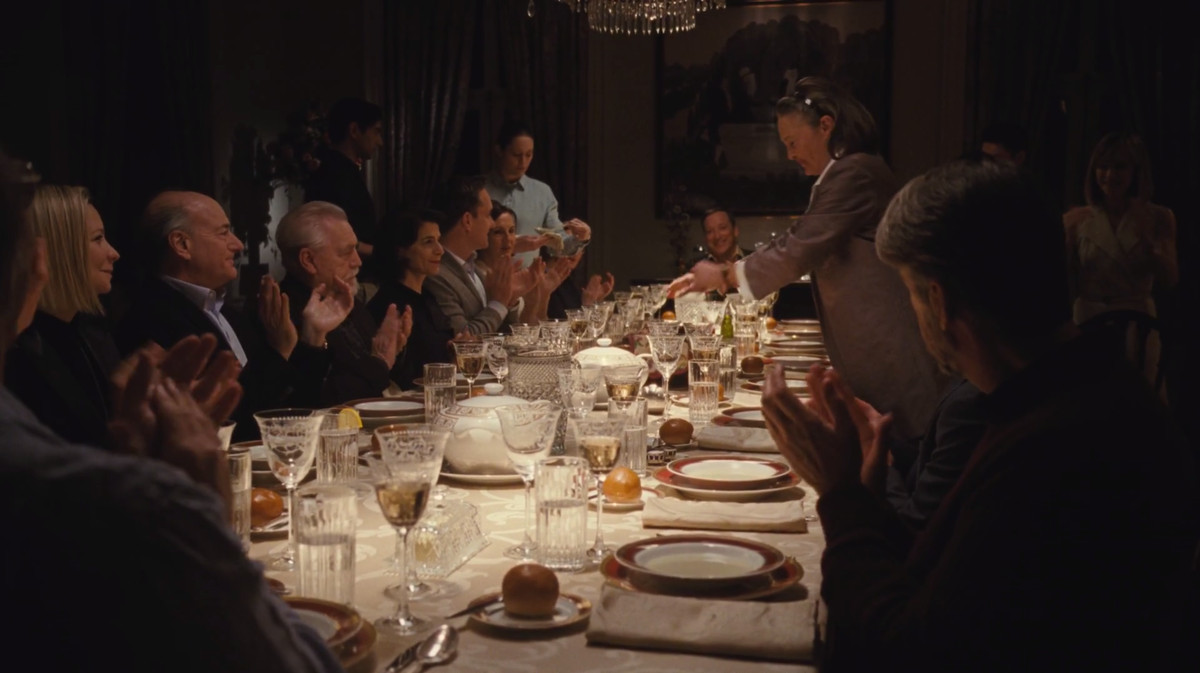 Succession screenshot: the Roys and the Pierces seated at a dining table with fine china.