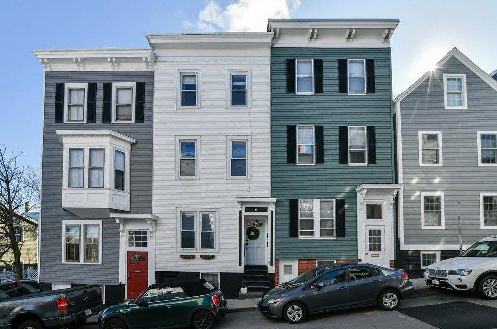 Three rectangular three-story townhouses in a row on a sidewalk.
