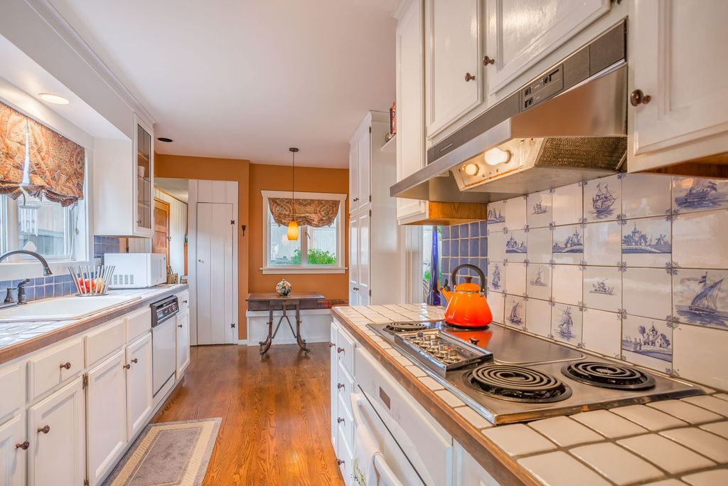 A kitchen with a built-in range with an orange kettle on it. White and blue backsplash tile have designs on them.