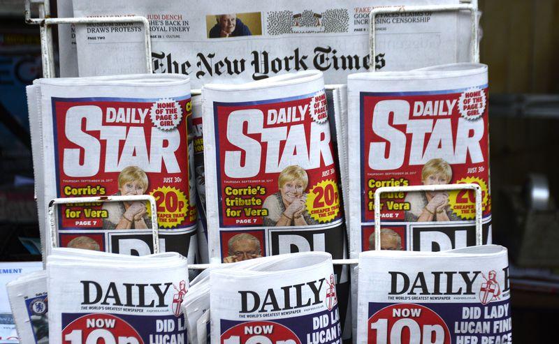 A newsstand rack featuring British tabloids.