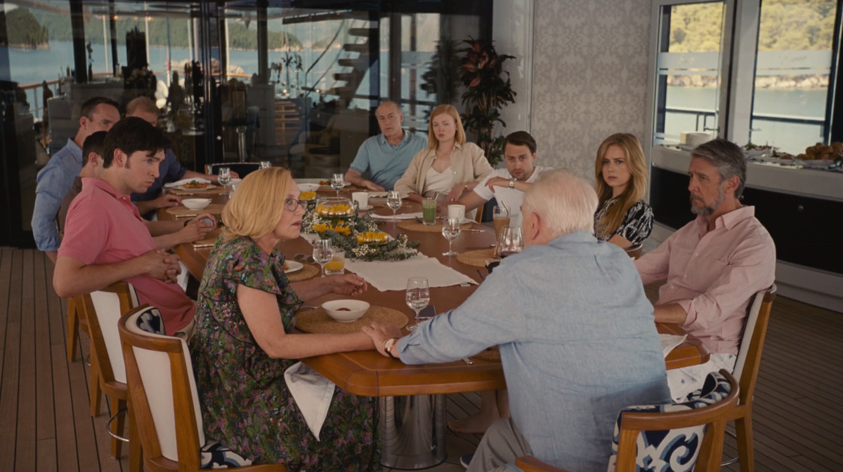 Succession screenshot: Karl, Tom, Kendall, Greg, Gerri, Connor, Willa, Roman, Shiv, and Frank seated around a dining table, with Logan at the head of the table.