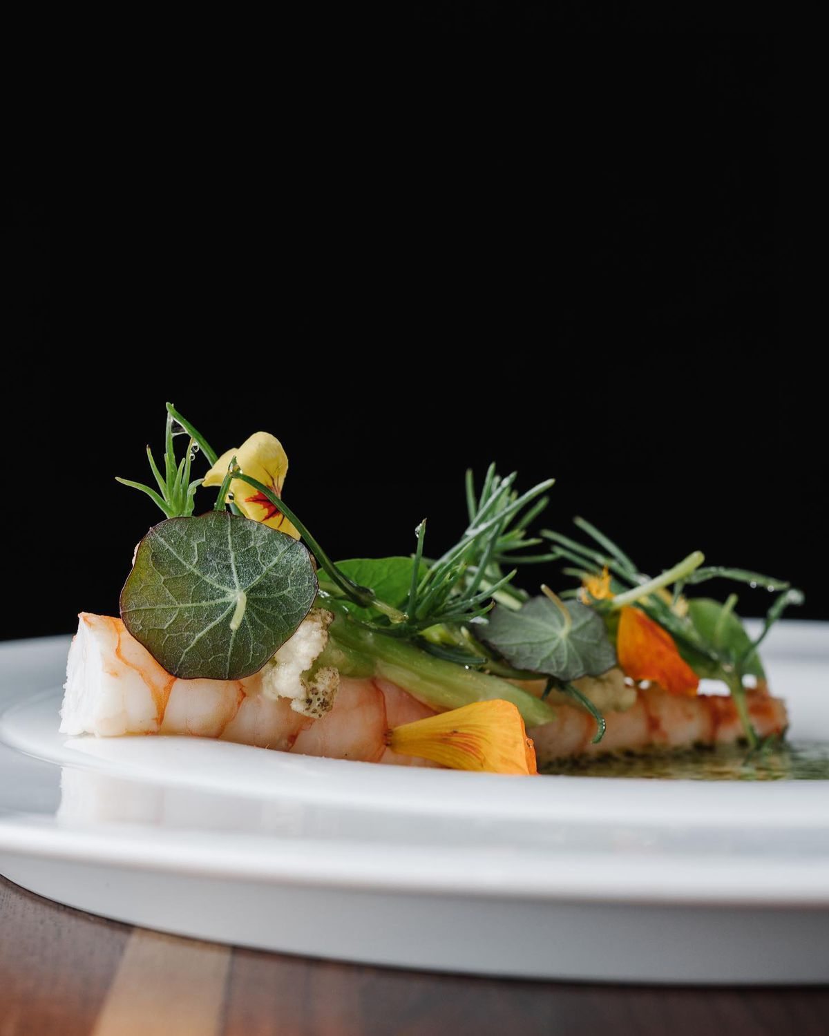 A plate of two poached shrimp topped with herbs and edible flowers