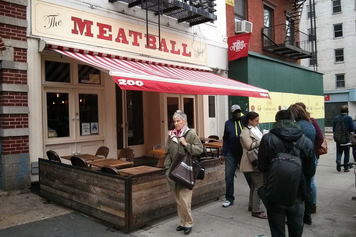 A restaurant exterior with a red sign that reads the Meatball Shop against a cream backdrop. There's a red and white striped awning that covers some sidewalk patio seating in front of the restaurant.
