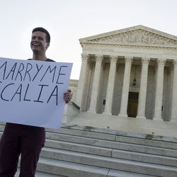 Ryan Aquilina, 24, of Washington holds a sign in front of the Supreme Court in Washington, Tuesday, April 28, 2015. The Supreme Court heard historic arguments in cases that could make same-sex marriage the law of the land.