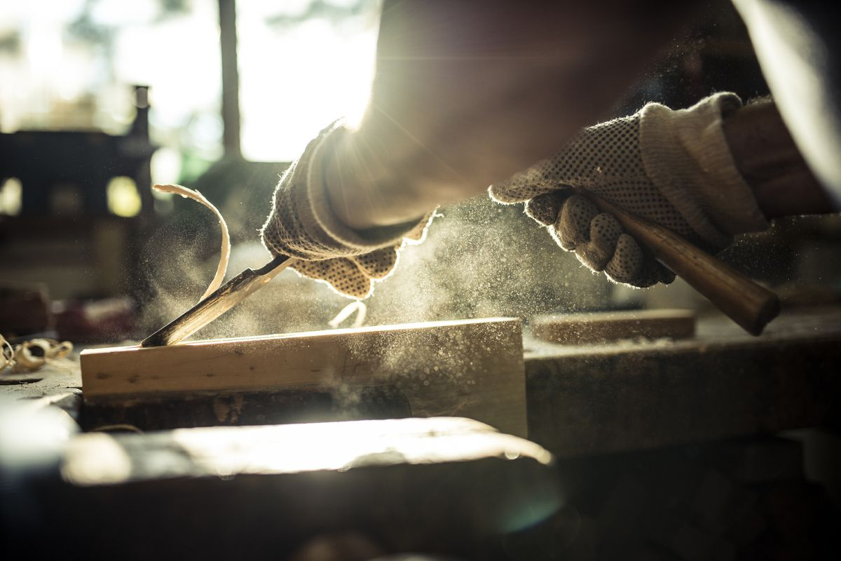 A person carving wood in a carpentry workshop.