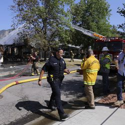 Emergency responders work at the scene of a house fire in Millcreek on Thursday, July 9, 2020. The fire is the third structure fire on this block in a week, and the second fire at the same house. Four houses in total have been damaged in the week's fires.