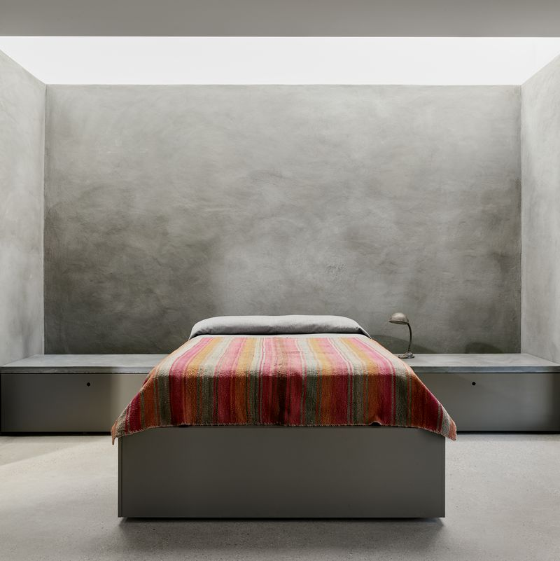 A bed with reddish bedding sits against a concrete wall.
