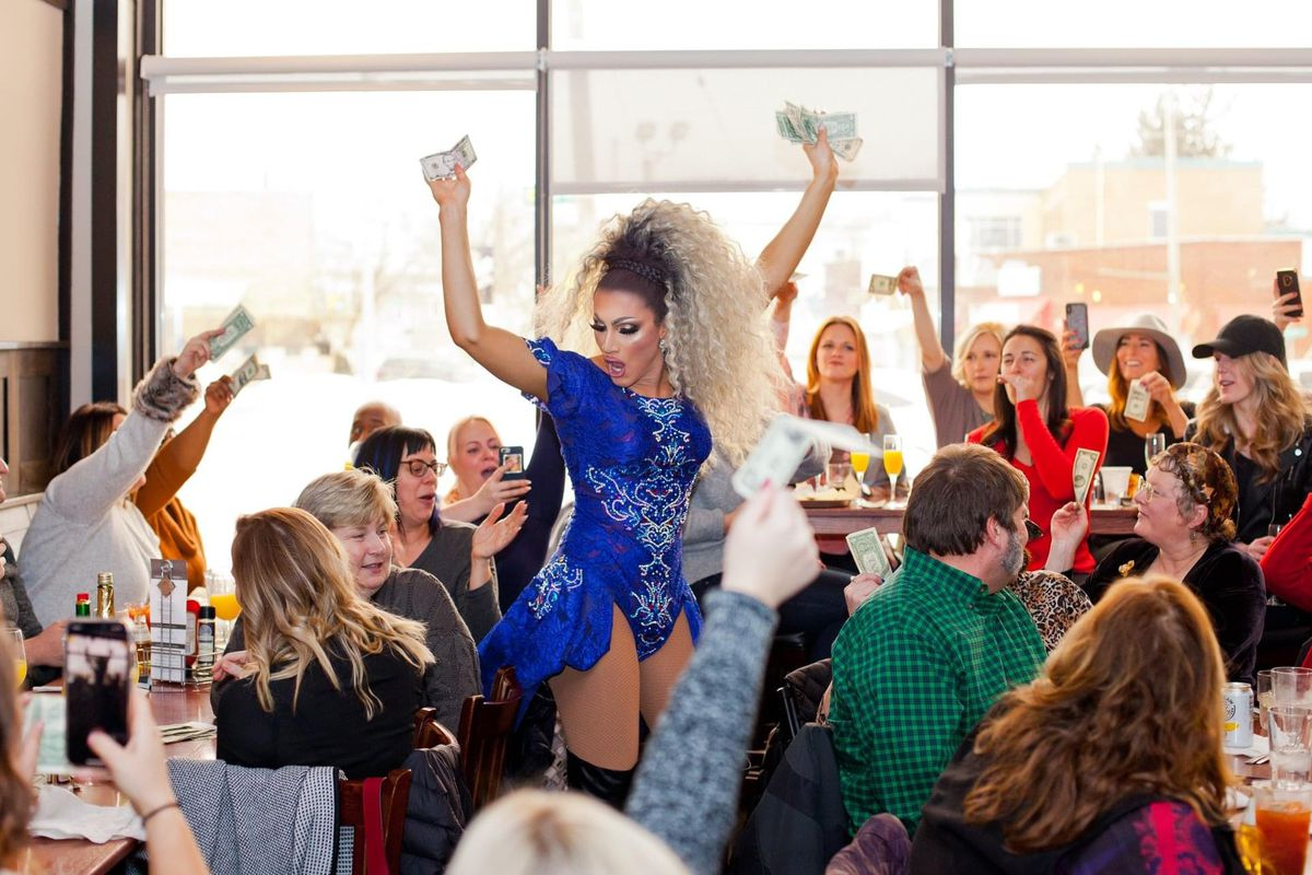 Gabriella Stratton Galore holds up her arms filled with cash as a crowd holds up dollar bill tips. She's wearing her long blonde hair tied back and a blue sequined leotard.