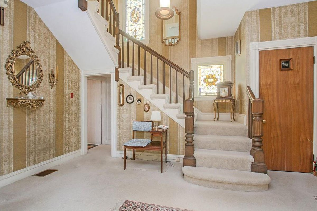 The plush entry foyer of a house with a staircase leading from it.
