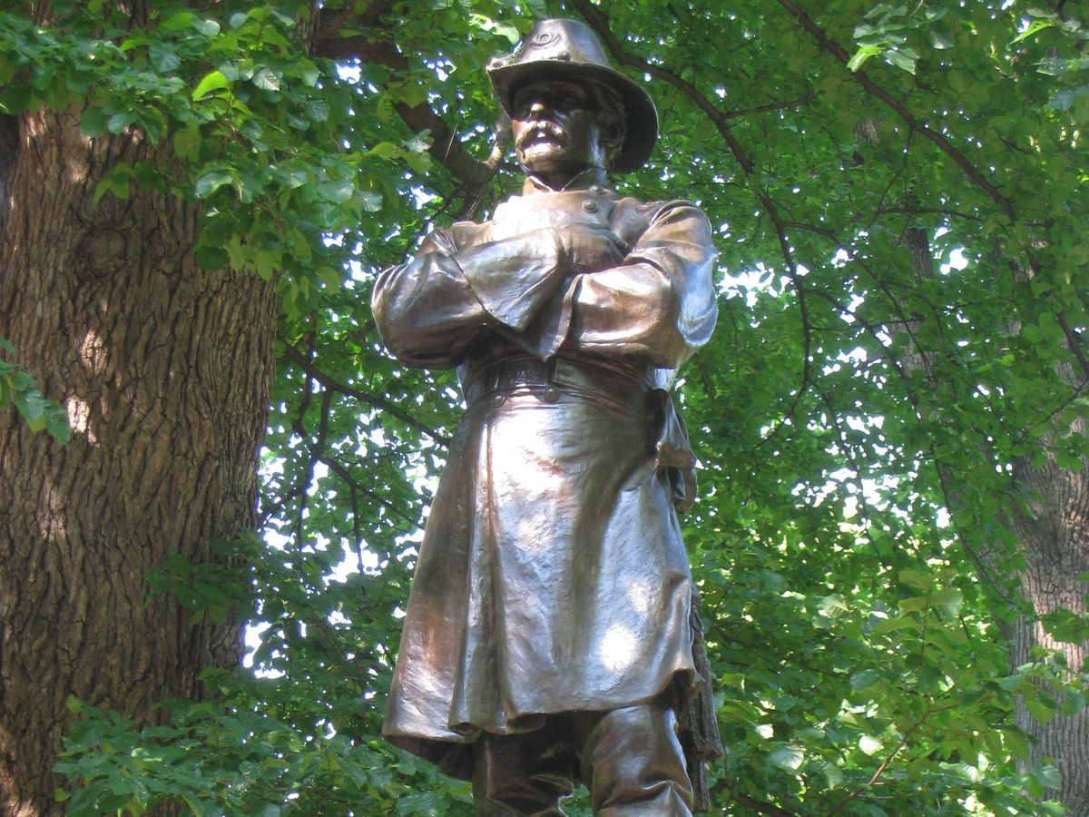 Bronze statue of a man with his arms folded and a hat on his head.