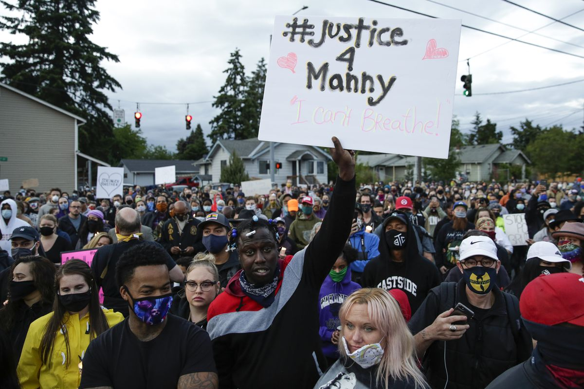 "A diverse, masked crowd is packed onto a street under a cloudy sky. A black man with short braids stands at the front of the group, and raises a white sign with black letters and pink hearts reading, ""#Justice 4 Manny."""