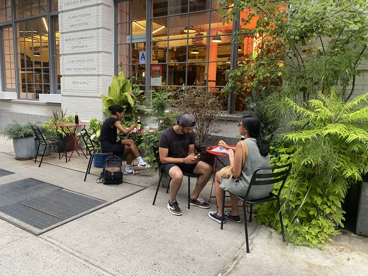 Patrons dine outside of Very Fresh Noodles at one of three tables, flanked by greenery