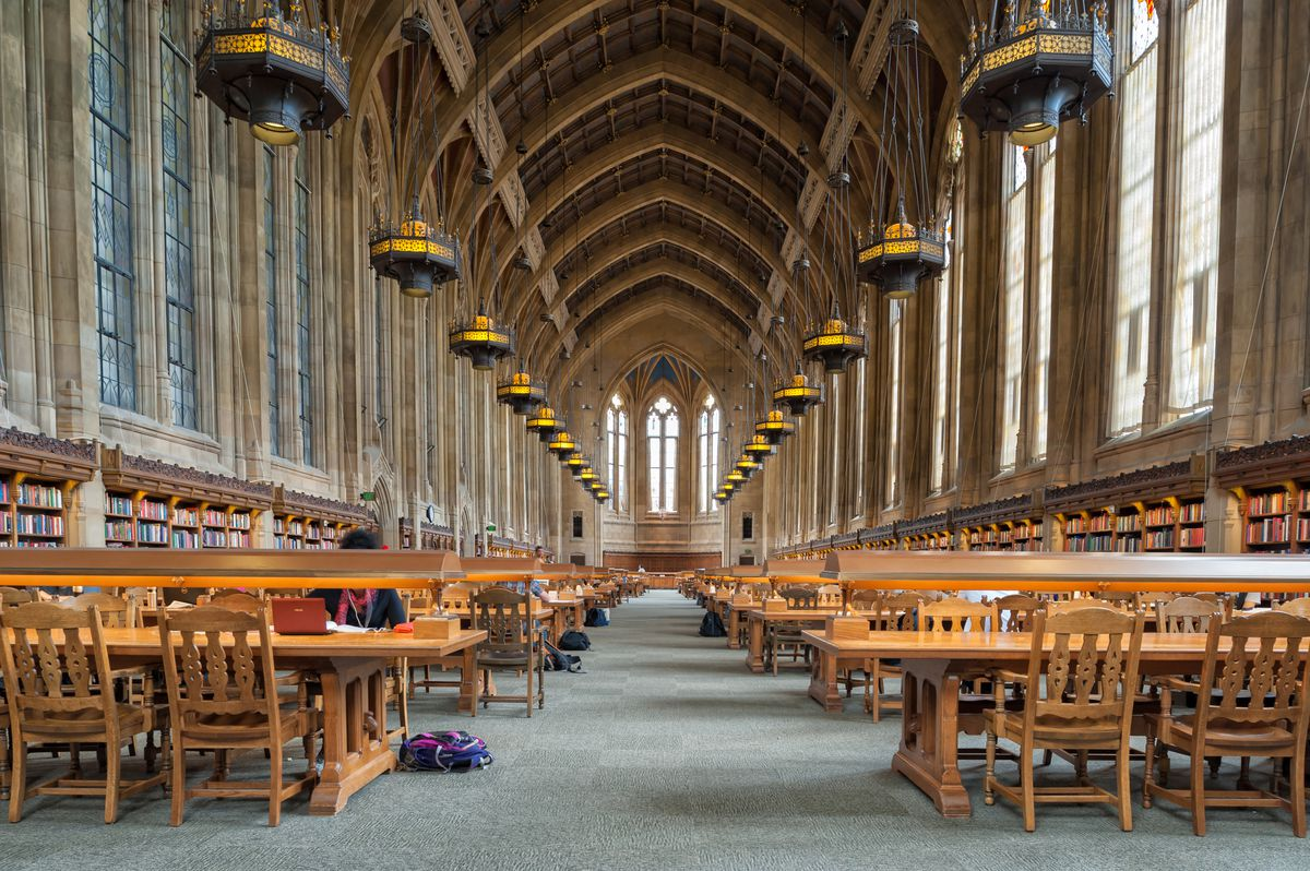 The interior of the Suzzallo Library in Seattle. There are rows of tables and chairs on the floor. There are chandeliers hanging from the ceiling over the tables. The ceiling is vaulted.