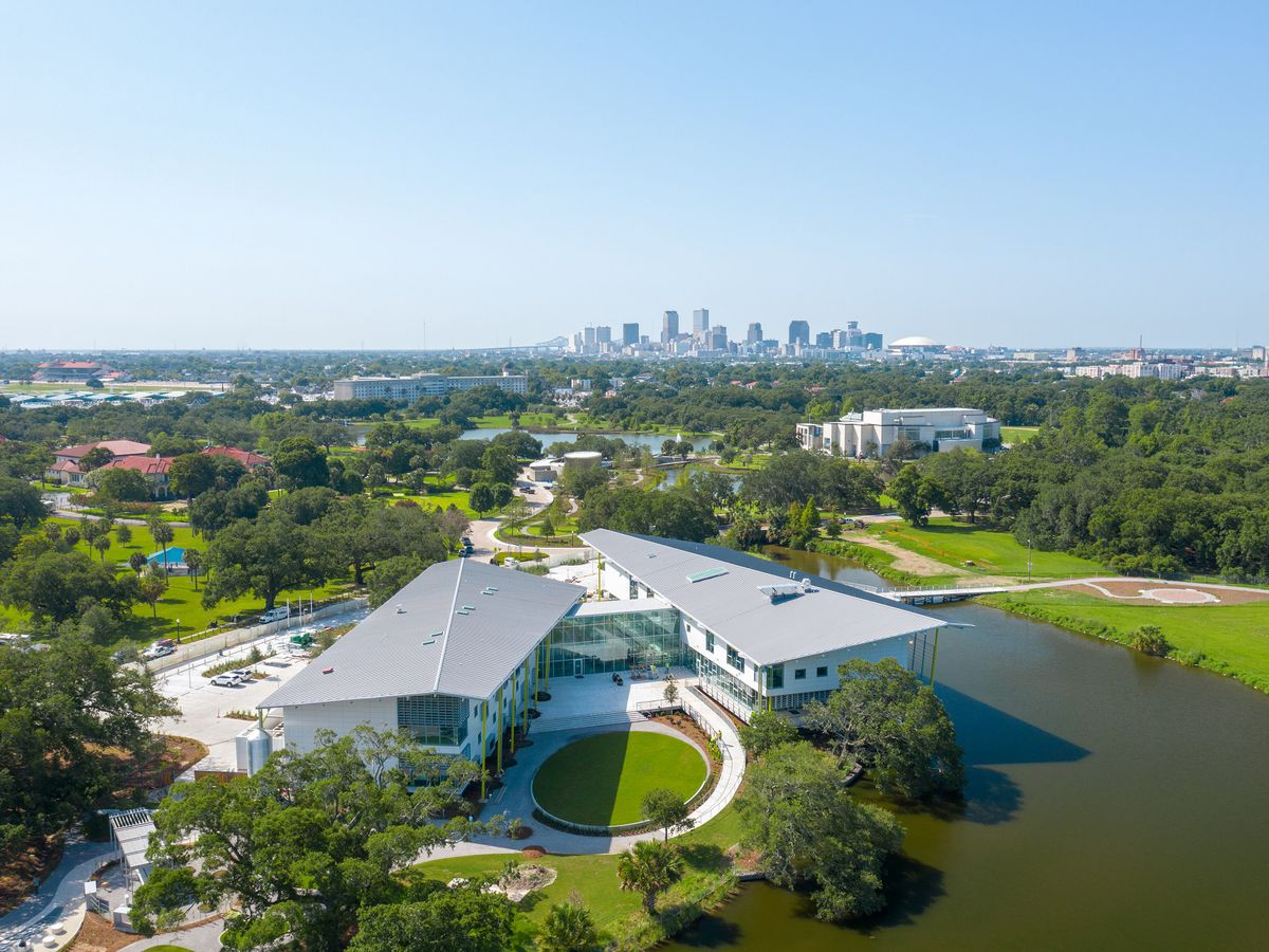 An aerial view of a modern-looking museum surrounded by trees and lagoons.