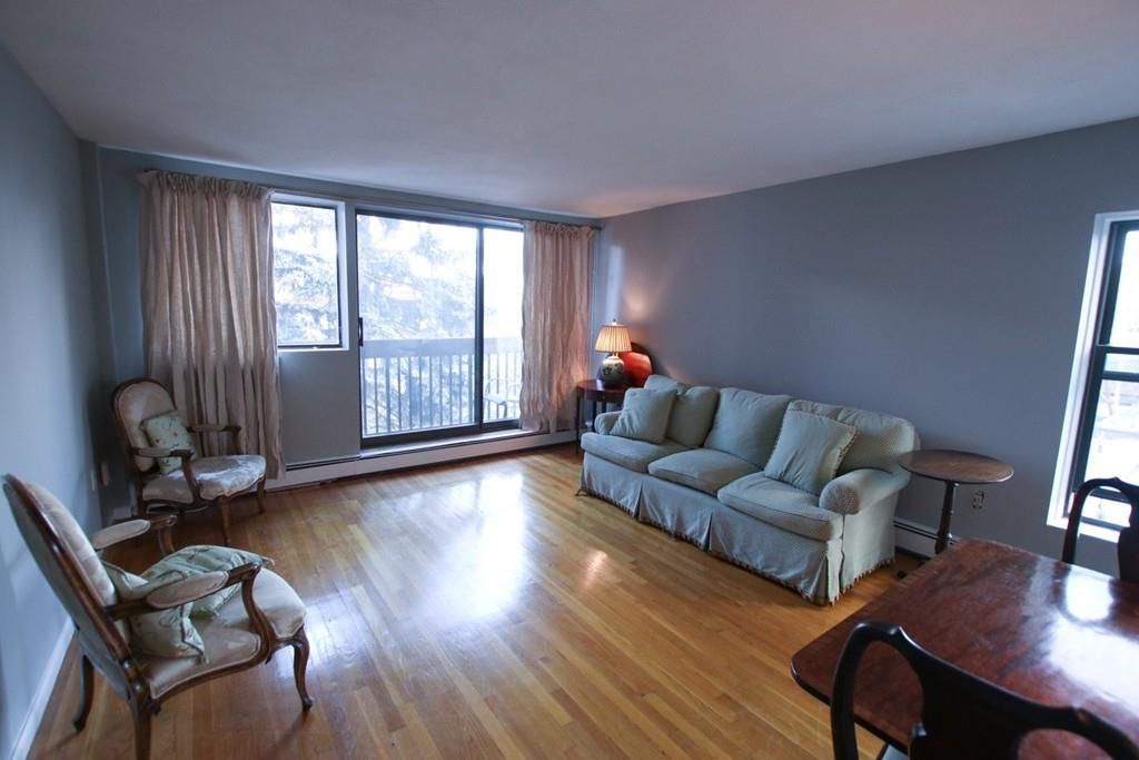 A living room with a couch and two chairs, and there's a sliding glass door at the end.
