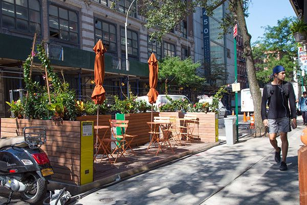 Wooden planks on the street hold orange outdoor tables and umbrellas, as a man walks by on the sidewalk
