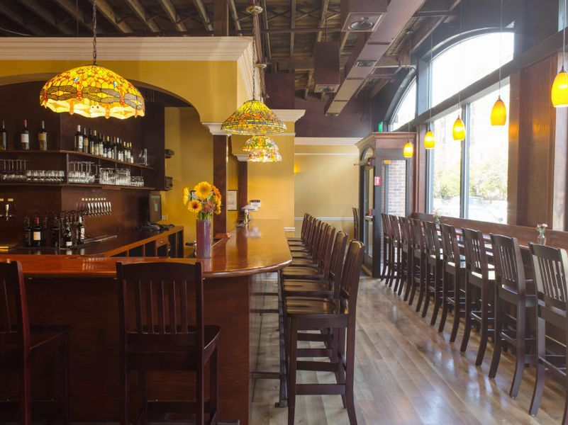 A warm wooden bar at a restaurant with yellow walls and Tiffany lamps.