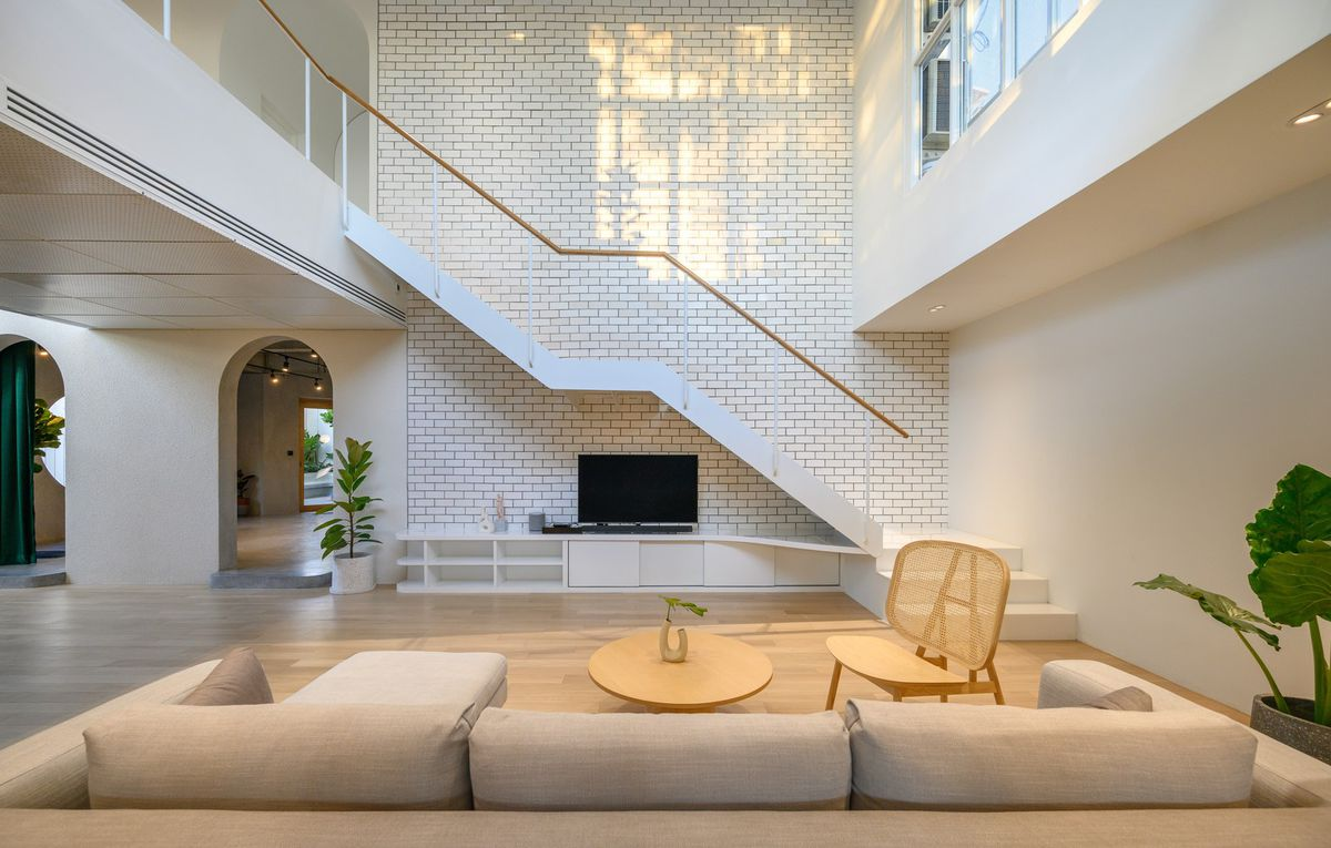 Light filled living room with white brick walls and floating staircase.