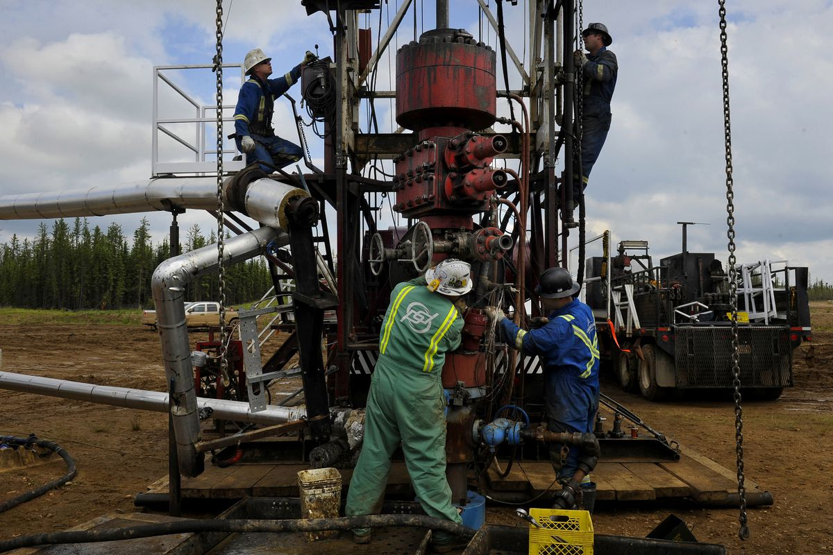 Canadian roughnecks set up an oil rig in Alberta