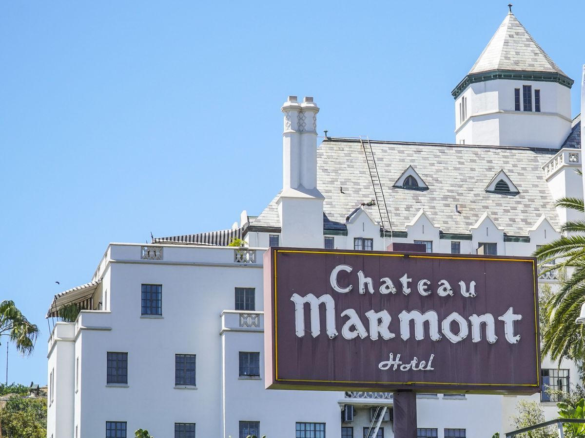 A large white building that resembles a castle. There is a tower on top the building. Outside the building is a sign that reads Chateau Marmont Hotel.