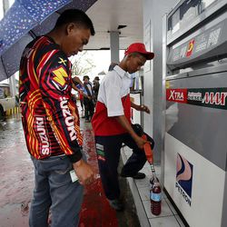 Jadmar Castillo pumps gasoline in Tacloban, Friday, Nov. 22, 2013. Some gas stations are reopening following a typhoon.