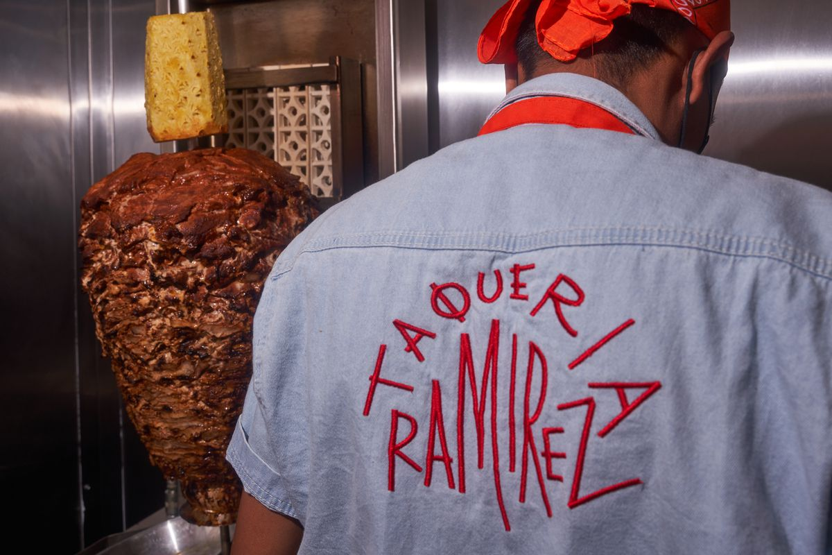 A man wearing a blue shirt with the words Taqueria Ramirez hand-stitched in red lettering stands behind an al pastor spit