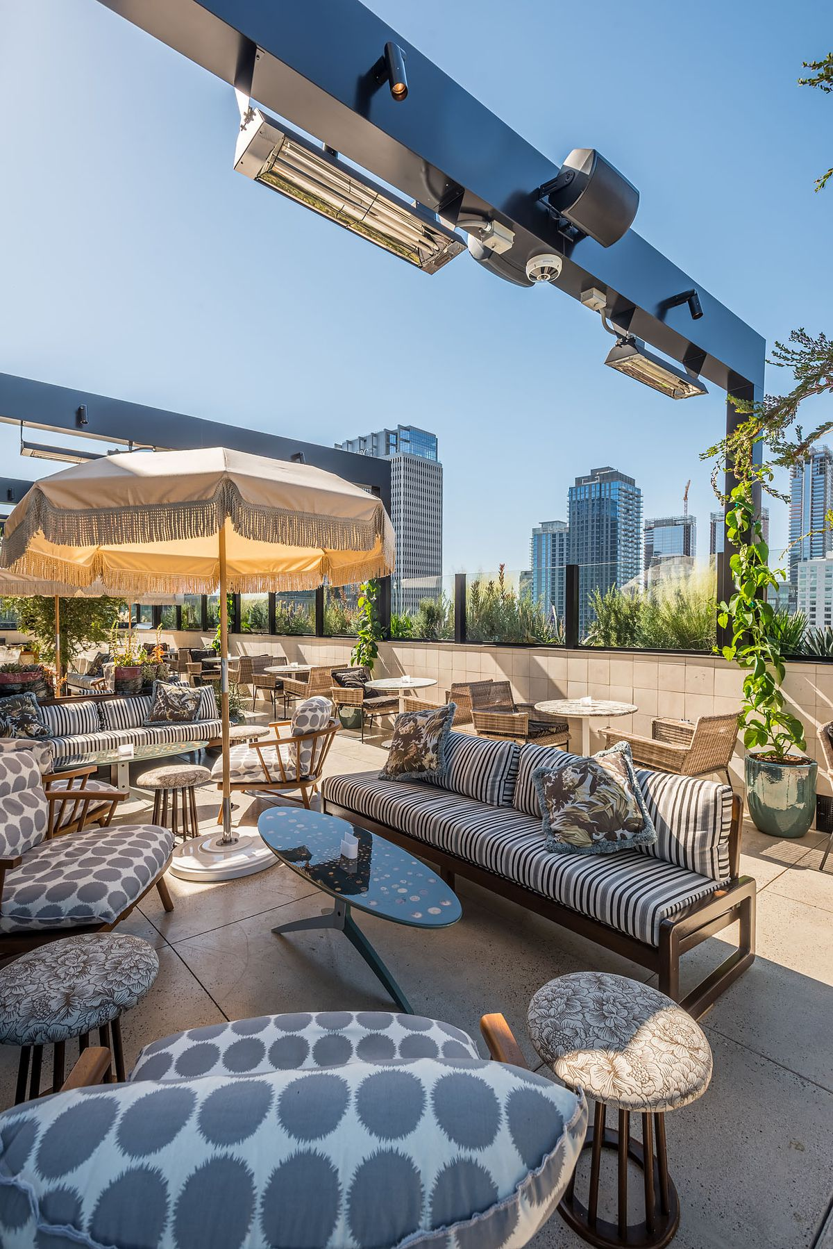 A shaded rooftop bar with tufted seating.