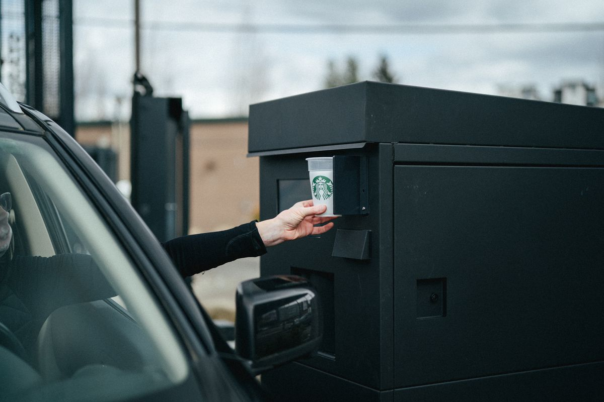 A woman in a surgical mask reaches out from the window of her car to place a Starbucks cup filled with milk at a black kiosk.