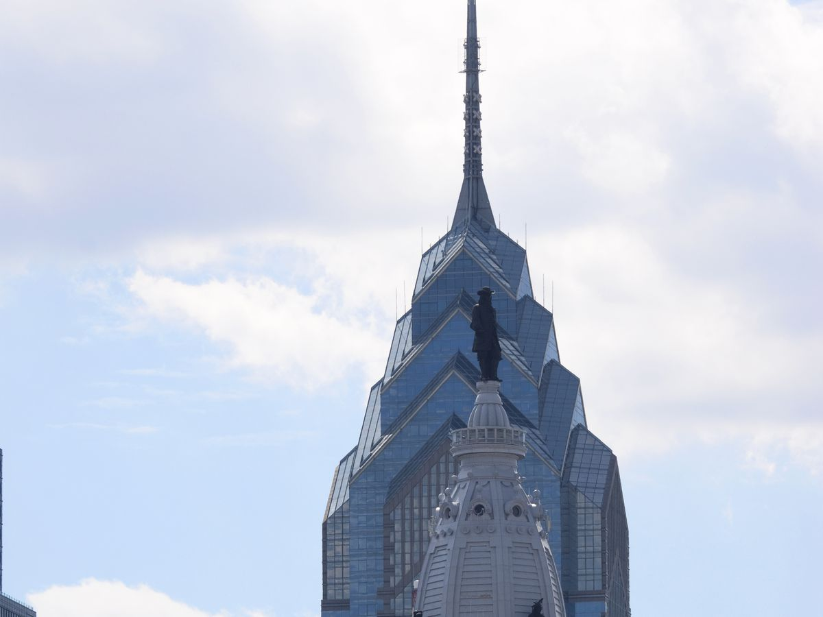 The top of a tall skyscraper in Philadelphia, One Liberty Place. The design is geometric and the facade is glass.