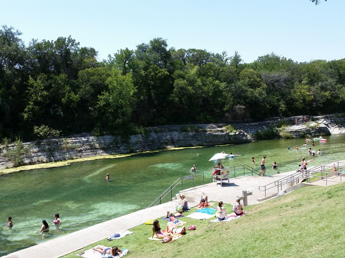 A large springs pool. There is a lawn in the foreground with many people. In the distance are trees.