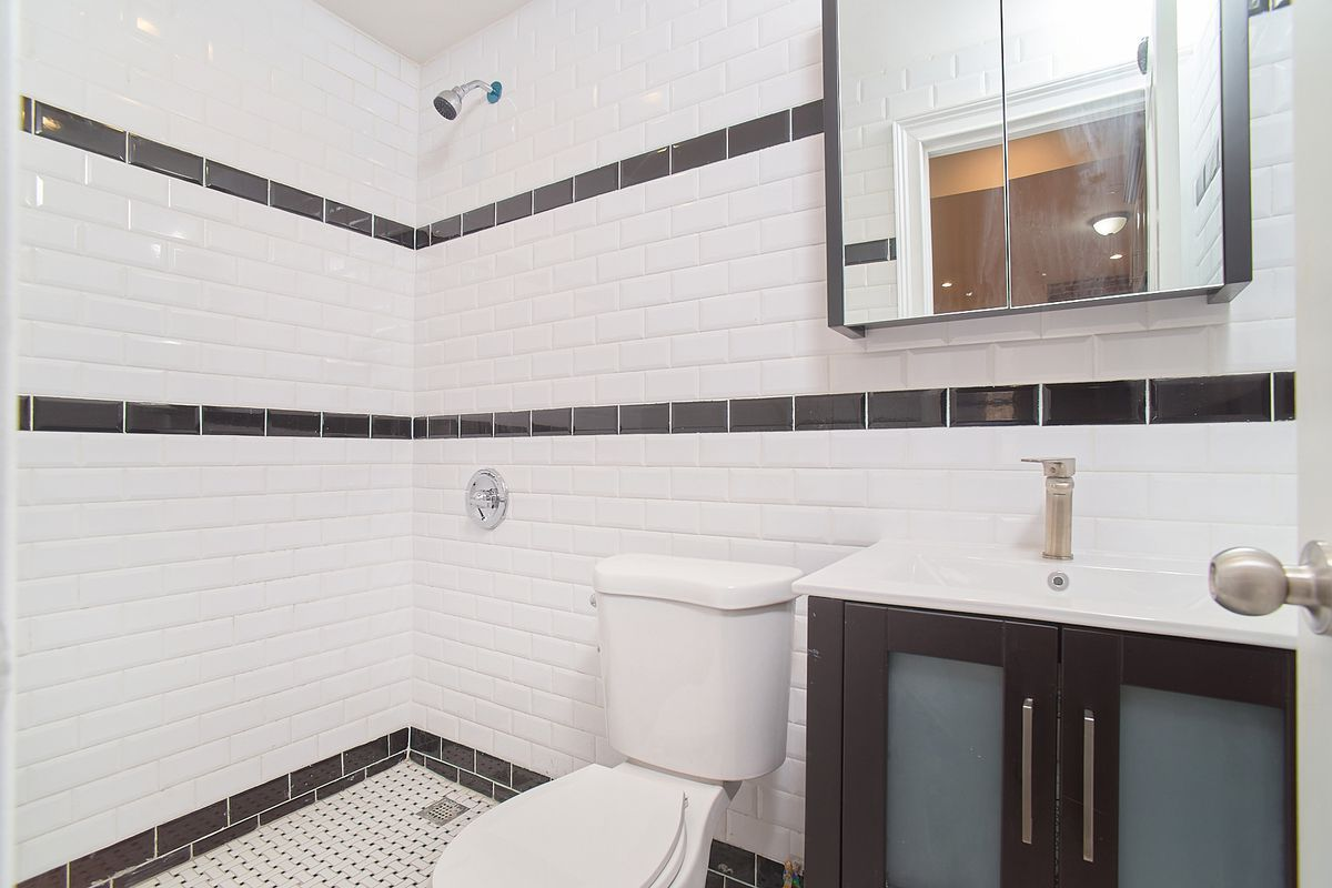 A bathroom with black and white tiles.