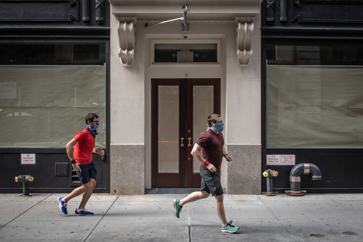 Two runners can be seen outside a storefront that has been covered up from the inside