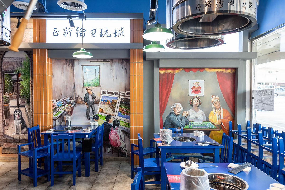 Inside Malubianbian's dining room in Rowland Heights with colorful murals and blue chairs and tables.