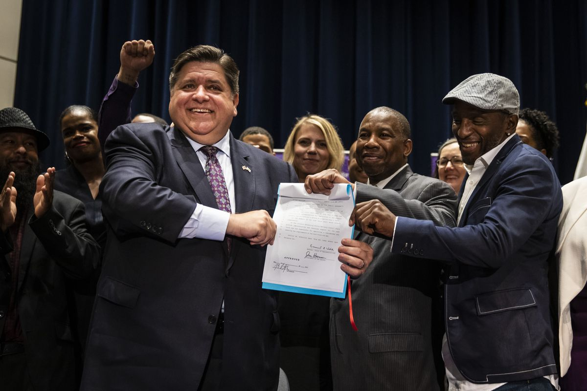 Flanked by supporters, Gov. J.B. Pritzker signs criminal justice legislation at Northwestern's Pritzker School of Law, barring the use of deceptive interrogation practices with minors and allowing county prosecutors the ability to petition to resentence someone, Thursday morning, July 15, 2021.