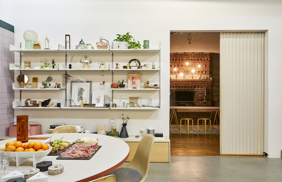 In the foreground, a table with some appetizers on it, oranges, a cheeseboard and fruit. Behind the table is a wall with shelves full of different objects, and next to the shelf is a sliding door to a room containing a fireplace.