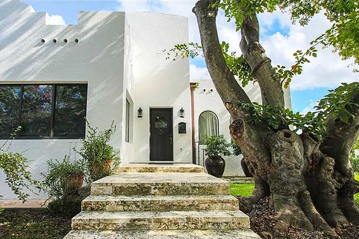 A Greek-looking home in Coral Way with white walls, and limestone steps