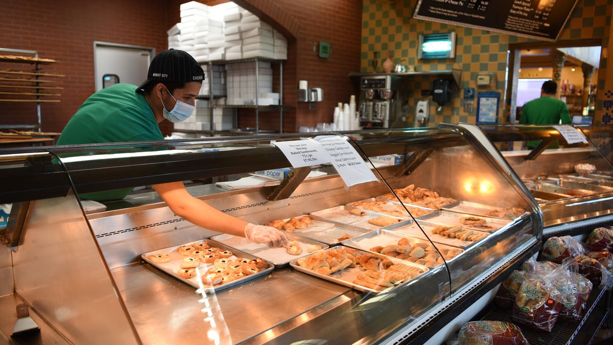 A masked male employee wearing a hat reaches into the pastry case at New Yasmeen Bakery in Dearborn.